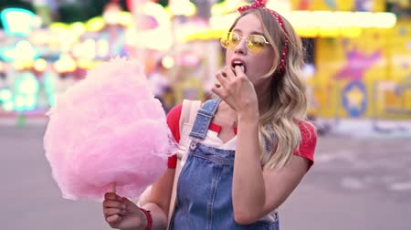 saç bantı : Attractive smiling young blonde woman enjoying eating candy floss while walking at amusement park