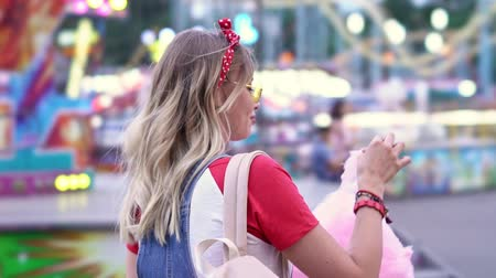 saç bantı : Side view of cheerful cute young blonde woman walking at amusement park and enjoying eating cotton candy
