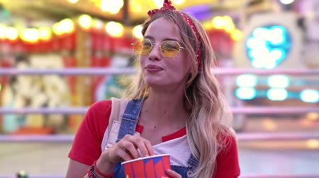 headband : Happy young blonde woman smiling and eating popcorn while staying near carousels in the amusement park Stock Footage