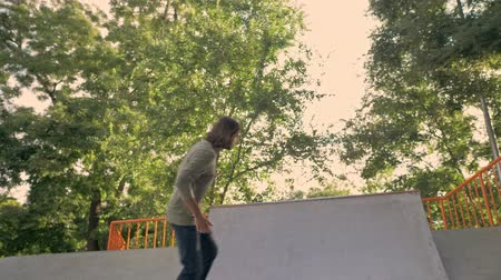 Деятельность выходные : Beautiful confident young bearded man riding on his skateboard at the ramp in the skatepark