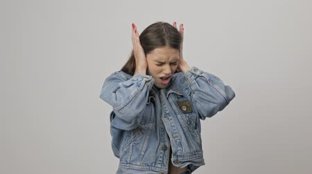 listens : Annoyed young brunette woman in denim jacket covering her ears with hands and shaking head while looking at the camera over gray background isolated Stock Footage