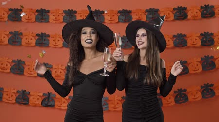 ijesztő : Cute smiling young witch women in black halloween costumes dancing under confetti and clinking glasses with champagne over orange pumpkin wall Stock mozgókép