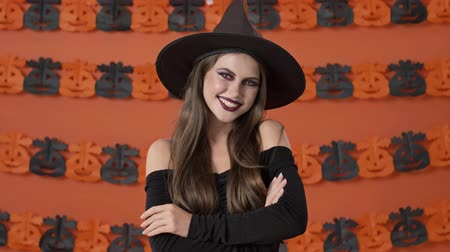 ijesztő : Cute cheerful young witch woman in black halloween costume smiling with crossed arms while looking at the camera over orange pumpkin wall