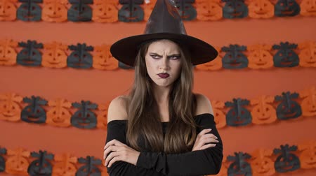 přestupek : Displeased young witch woman in black halloween costume taking offense at someone and crossing her arms while looking at the camera over orange pumpkin wall