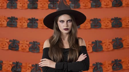 hat : Serious pretty young witch woman in black halloween costume saying no and shaking her head negatively over orange pumpkin wall Stock mozgókép