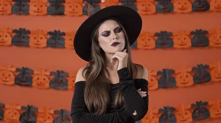 chapeau sorciere : Pensive cute young witch woman in black halloween costume thinking about something and touching her chin over orange pumpkin wall
