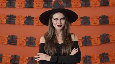 mascarada : Happy attractive young witch woman in black halloween costume saying yes and shaking her head approvingly over orange pumpkin wall