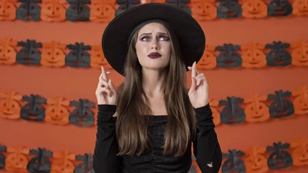 remény : Attractive young witch woman in black halloween costume crossing her fingers with hope and asking for something while looking up over orange pumpkin wall
