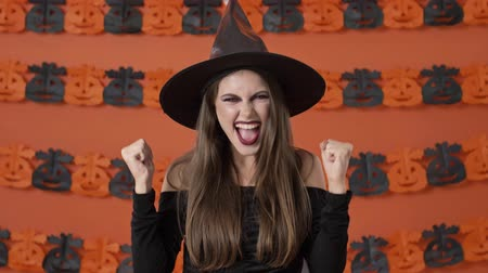 büyücü : Cheerful pretty young witch woman in black halloween costume making winner gesture with hands over orange pumpkin wall Stok Video