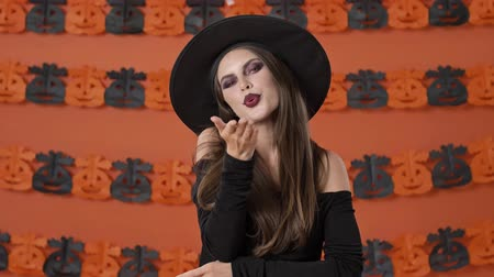 feiticeiro : Beautiful flirty young witch woman in black halloween costume smiling and blowing a kiss with hand to the camera over orange pumpkin wall