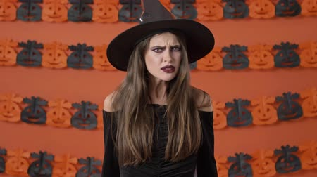 přestupek : Displeased beautiful young witch woman in black halloween costume getting angry and taking offense at someone over orange pumpkin wall