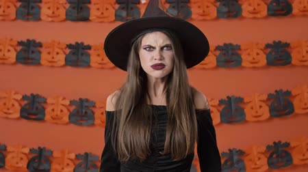 mascarada : Pretty aggressive young witch woman in black halloween costume screaming loudly over orange pumpkin wall Archivo de Video