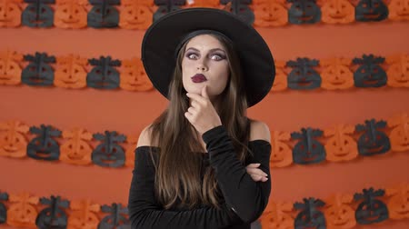 chapeau sorciere : Cheerful concentrated young witch woman in black halloween costume thinking about something and making idea gesture over orange pumpkin wall