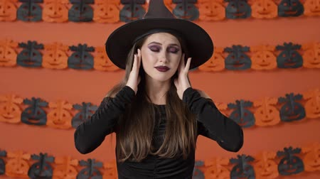 pokrývka hlavy : Unhappy beautiful young witch woman in black halloween costume covering her ears with hands and grimacing over orange pumpkin wall Dostupné videozáznamy
