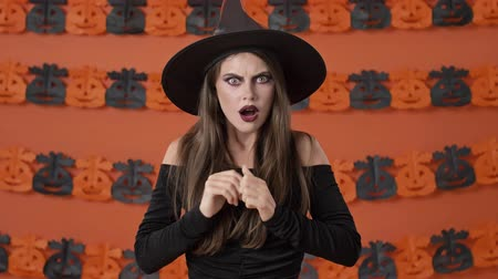 ijesztő : Displeased pretty young witch woman in black halloween costume becoming shocked and scared of something over orange pumpkin wall
