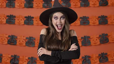 mascarada : Attractive happy young witch woman in black halloween costume smiling with crossed arms and becoming surprised of something over orange pumpkin wall
