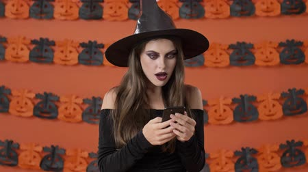 ijesztő : Shocked cute young witch woman in black halloween costume screaming and making winner gesture while using smartphone over orange pumpkin wall