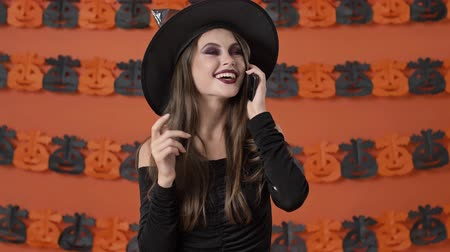仮面舞踏会 : Attractive happy young witch woman in black halloween costume smiling and laughing while talking on smartphone over orange pumpkin wall