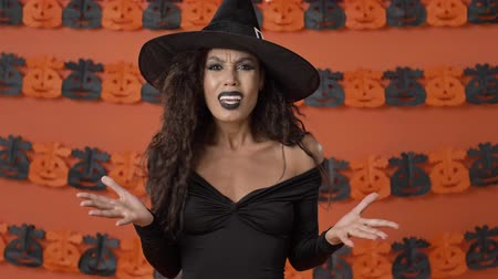 calabaza : Aggressive young witch woman in black halloween costume gesturing and having a dispute with someone while looking at the camera over orange pumpkin wall Archivo de Video
