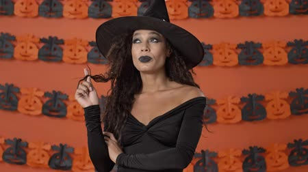 ijesztő : Pensive cute young witch woman in black halloween costume thinking about something and playing with her hair over orange pumpkin wall Stock mozgókép