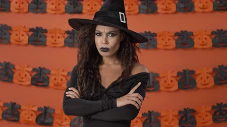 ijesztő : Angry beautiful young witch woman in black halloween costume crossing her arms and taking offense at someone over orange pumpkin wall Stock mozgókép