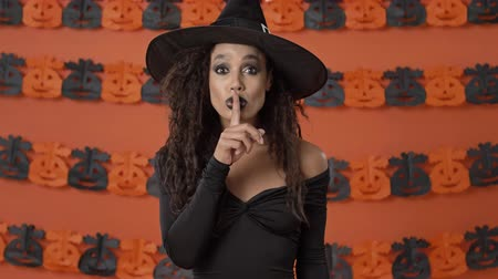 chapeau sorciere : Serious pretty young witch woman in black halloween costume showing silence gesture over orange pumpkin wall