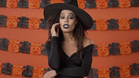 head over : Exhausted beautiful young witch woman in black halloween costume wiping sweat from forehead and massaging temples over orange pumpkin wall