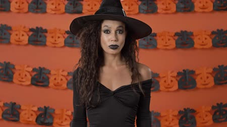 büyücü : Serious cute young witch woman in black halloween costume saying no and shaking her head negatively over orange pumpkin wall Stok Video