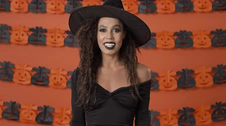 mascarada : Cute cheerful young witch woman in black halloween costume saying yes and shaking her head approvingly over orange pumpkin wall Archivo de Video