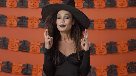 ijesztő : Beautiful emotional young witch woman in black halloween costume crossing her fingers with hope and asking for something over orange pumpkin wall