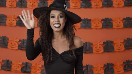 ijesztő : Cute cheerful young witch woman in black halloween costume waving with hand while looking at the camera over orange pumpkin wall