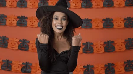 mascarada : Happy beautiful young witch woman in black halloween costume showing winner gesture with hands over orange pumpkin wall Archivo de Video