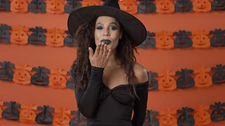 mascarada : Attractive flirty young witch woman in black halloween costume smiling and blowing a kiss with hand to the camera over orange pumpkin wall