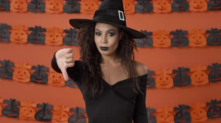 ijesztő : Displeased pretty young witch woman in black halloween costume making thumb down gesture and shaking her head negatively over orange pumpkin wall