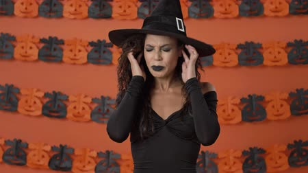 witch hat : Unhappy attractive young witch woman in black halloween costume plugging her ears with fingers and shaking her head negatively over orange pumpkin wall Stock Footage