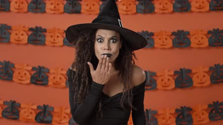 witch hat : Shocked displeased young witch woman in black halloween costume covering her mouth with hand and shaking her head negatively over orange pumpkin wall