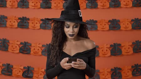ijesztő : Concentrated calm young witch woman in black halloween costume chatting on smartphone over orange pumpkin wall Stock mozgókép