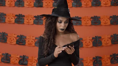 büyücü : Serious attractive young witch woman in black halloween costume becoming shocked and confused while using smartphone over orange pumpkin wall Stok Video