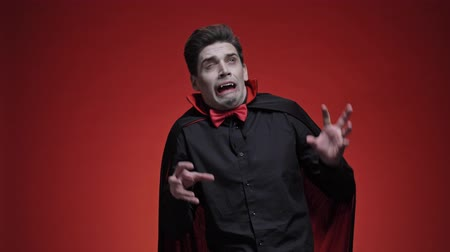 vampier : Terrified man dracula with fangs in black halloween costume becoming scared of light isolated over red wall Stockvideo