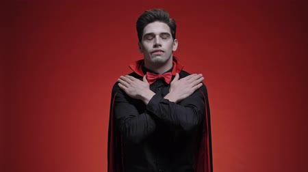 vampier : Sleeping man dracula with crossed hands in black halloween costume becoming scared of light  isolated over red wall