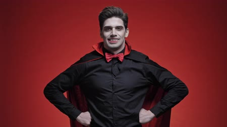 vampier : Vampire man with blood and fangs with hands on hips in black halloween costume is smiling isolated over red wall Stockvideo