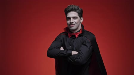 vampier : Vampire man with blood and fangs in black halloween costume is winking and smiling while looking at the camera over red wall isolated Stockvideo