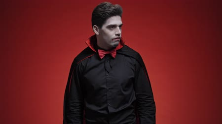 diabeł : Walking vampire man with blood and fangs in black halloween costume looking for something and feeling disappointed isolated over red wall Wideo