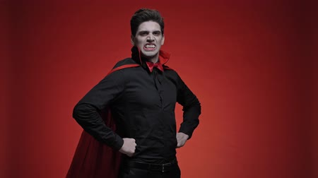 гул : Vampire man with blood and fangs with hands on hips in black halloween costume is roaring isolated over red wall Стоковые видеозаписи