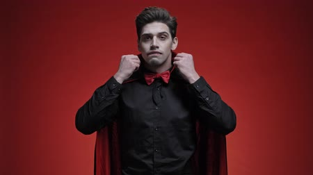 ijesztő : Vampire man with blood and fangs in black halloween costume is fixing his bow tie, collar, hair and teeth isolated over red wall Stock mozgókép