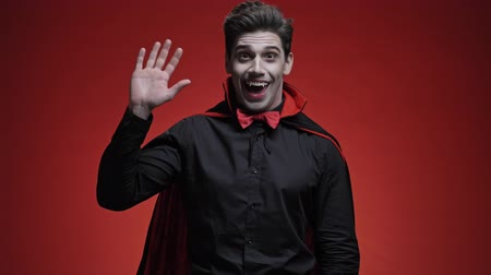 vampier : Happy and smiling vampire man with blood and fangs in black halloween costume waving hand to the camera isolated over red wall