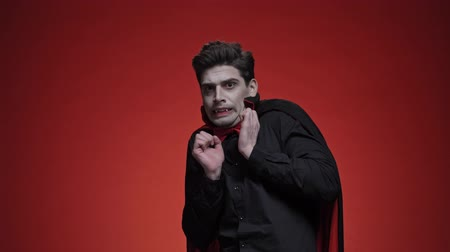 ijesztő : Vampire man with fangs in black halloween costume becoming scared isolated over red wall looking at the camera
