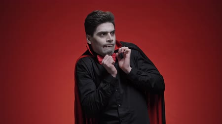 vampier : Displeased vampire man with fangs in black halloween costume becoming scared of something while looking away isolated over red wall