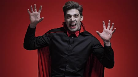 kükreme : Vampire man with blood and fangs in black halloween costume appearing with scary gesture over red wall Stok Video