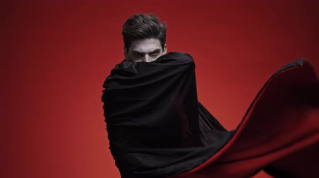 řev : Frightening vampire man with blood and fangs in black halloween costume wrapping in his cloak isolated over red wall